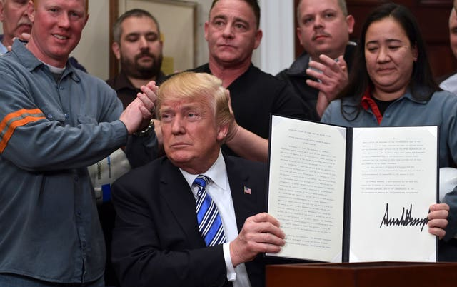 Donald Trump holds up a proclamation on steel imports (Susan Walsh/AP)