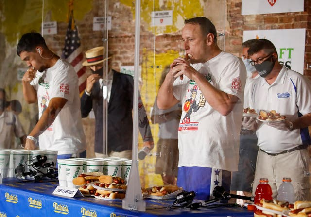 Competitive eater Joey Chestnut sets a new world record with 75 hot dogs to win the men's division of the Nathan's Famous July Fourth hot dog eating contest, Saturday, July 4, 2020, in the Brooklyn borough of New York