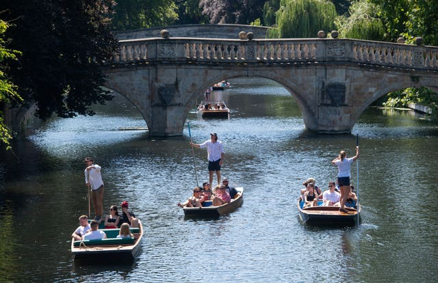 People enjoy the hot weather during a punt ride along the River Cam in Cambridge (Joe Giddens/PA)