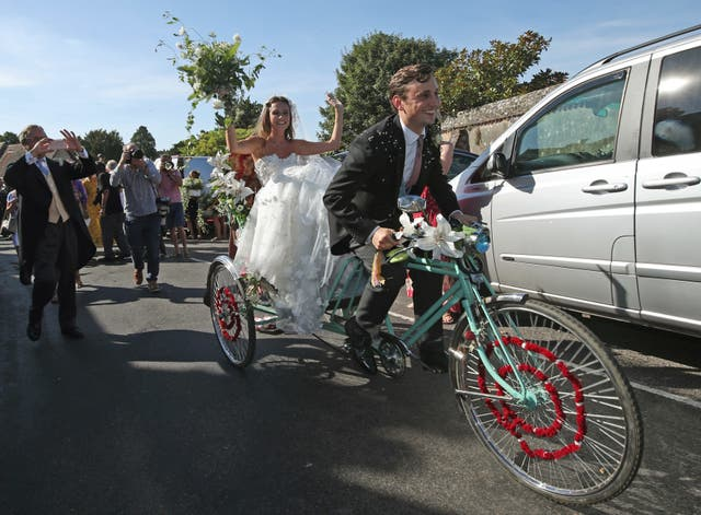 Charlie van Straubenzee rides a tricycle with his bride Daisy Jenks as a passenger