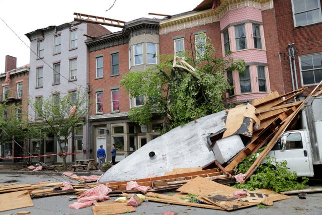 Men stand near buildings damaged by a storm in Newburgh, New York (AP)