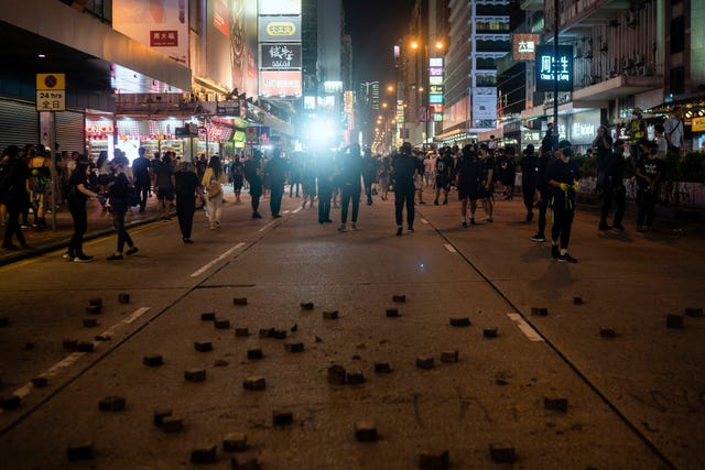 Riot police chase protesters near a demonstration in Hong Kong
