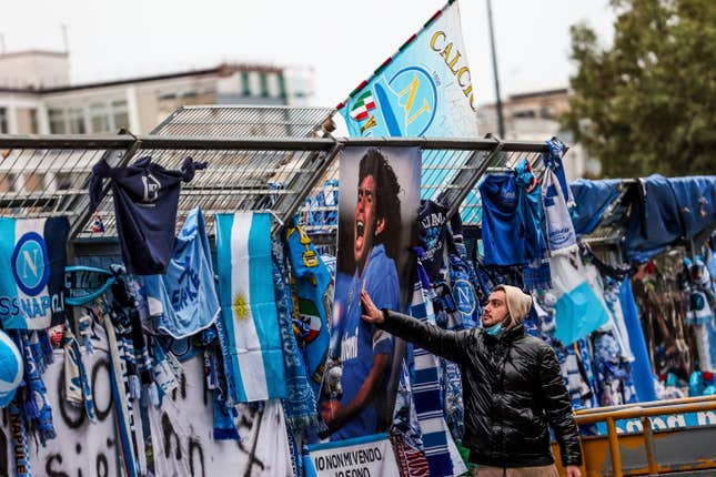 A fan touches a photo of Diego Maradona hanging on the gates of Napoli's stadium