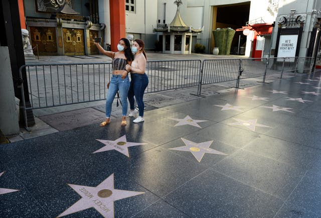 Mercedes Mejia, left, and Coralia Hernandez pose for a selfie in front of the still-closed courtyard of the TCL Chinese Theatre on Hollywood Boulevard in Los Angeles