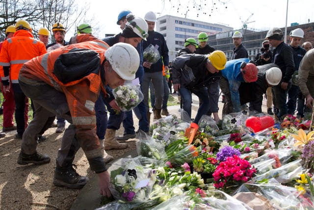 Construction workers who witnessed Monday's shooting incident in a tram put flowers at the site in Utrecht