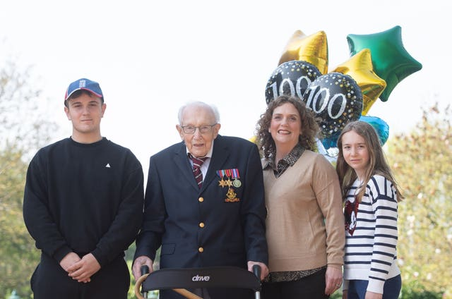 99-year-old war veteran Captain Tom Moore, with (left to right) grandson Benji, daughter Hannah Ingram-Moore and granddaughter Georgia, at his home in Marston Moretaine, Bedfordshire, after he achieved his goal of 100 laps of his garden – raising more than 14 million pounds for the NHS. Joe Giddens/PA Wire