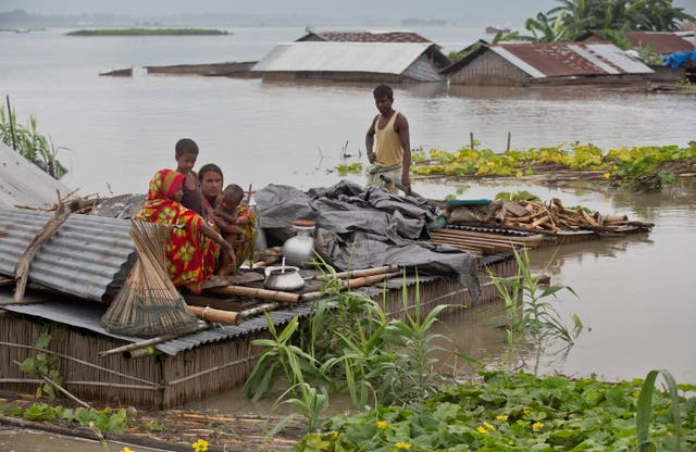Flood-affected villagers take shelter on the roof of their submerged houses in Katahguri village along the river Brahmaputra, east of Gauhati, India