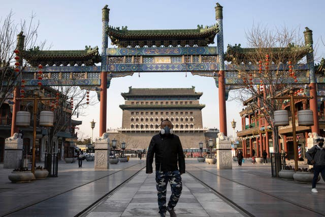 A man wearing a face mask walks through a quiet retail district in Beijing