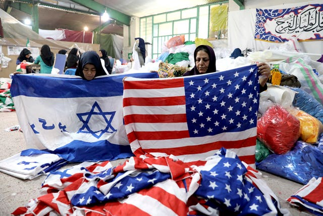 Workers fold US and Israeli flags