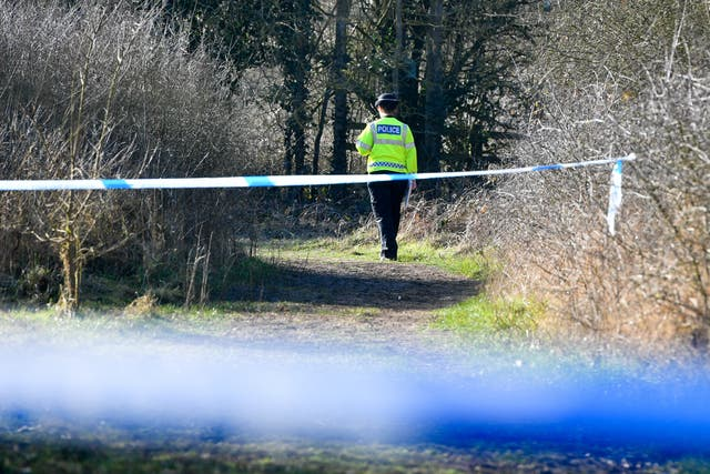 A police officer behind two police cordons in woodland at Pentylands Park, Highworth, where police are searching following a tip-off (Ben Birchall/PA)