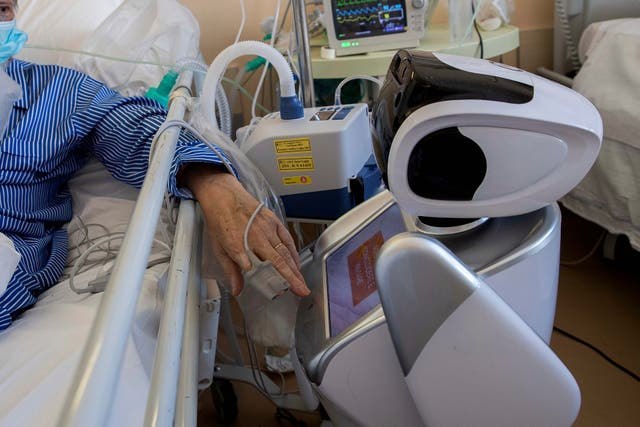 A coronavirus patient under treatment in intensive care interacts with a robot in Varese, Italy