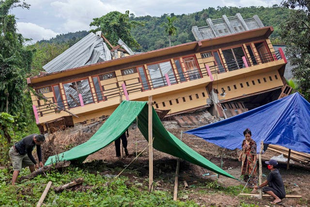 Residents build tents outside their badly damaged house in Mamuju