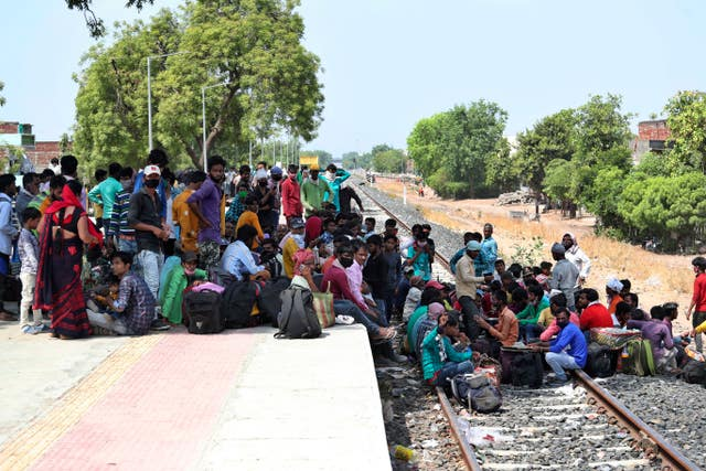 Migrant workers from other states desperate to return to their homes gather near a train station in Ahmedabad, India