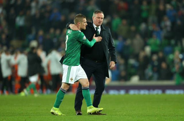 Steven Davis, who missed a penalty, and manager Michael O'Neill, who is stepping down to join Stoke, embrace after Northern Ireland's draw with Holland
