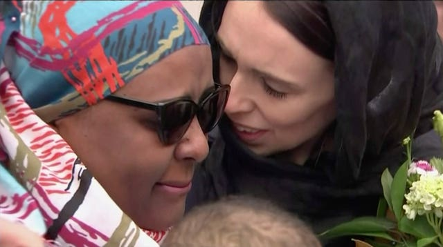 New Zealand's Prime Minister Jacinda Ardern hugs and consoles a woman as she visited Kilbirnie Mosque to lay flowers