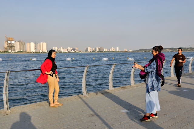Women take a picture while spending an afternoon around the Persian Gulf Martyrs' Lake in Tehran