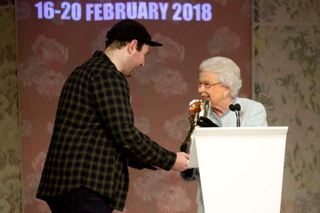 The Queen presents the award to Richard Quinn (Isabel Infantes/PA)