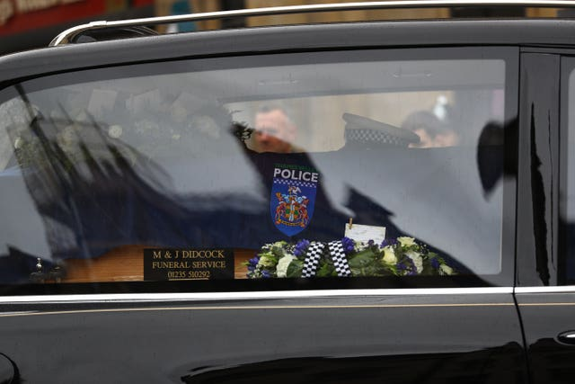 The funeral cortege passes through the streets of Oxford