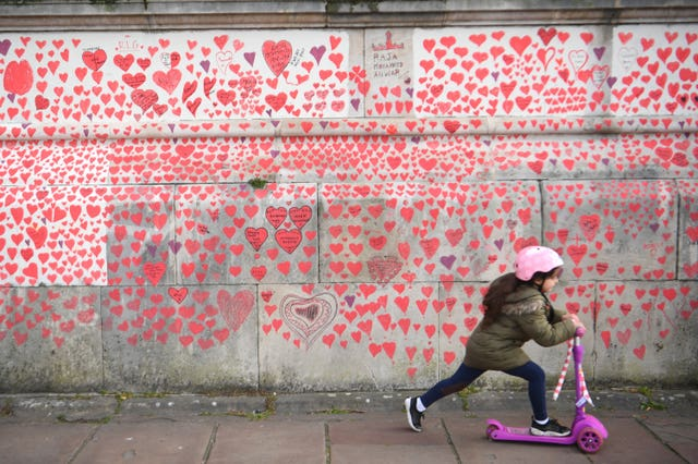 A young girl rides a scooter past the National Covid Memorial Wall