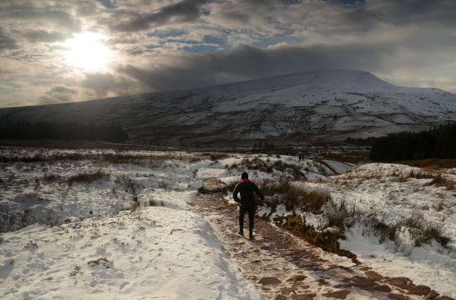People walk a snowy path in the Brecon Beacons