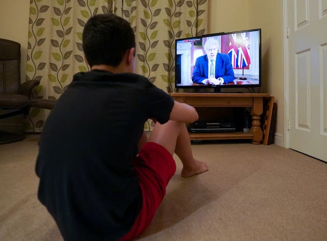 A family member in Nottingham watches Prime Minister Boris Johnson making a televised address to the nation