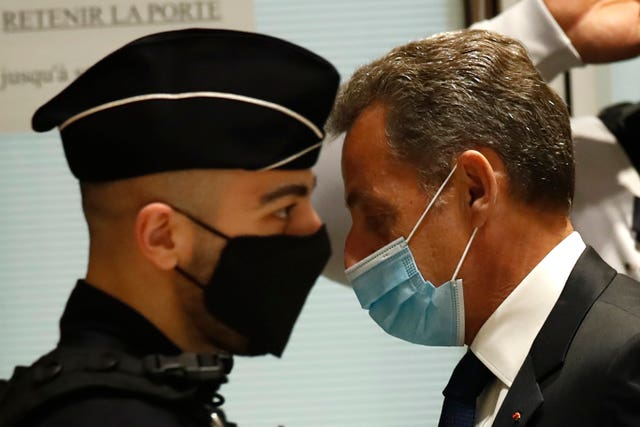 Sarkozy, right, arrives at the courtroom in Paris