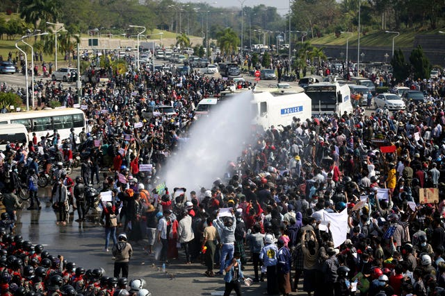 A police truck uses a water cannon to disperse a crowd of protesters in Naypyitaw, Myanmar