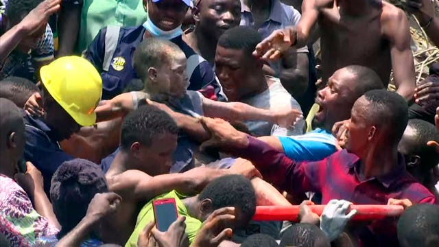 People help a child after he was rescued from the scene of a building collapse in Lagos