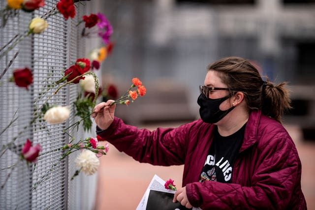 Flowers were placed on the fence in front of the Hennepin County Government Centre by Stacey Bornholdt a day before jury selection is set to begin in the trial of former Minneapolis officer Derek Chauvin, who is accused of killing George Floyd