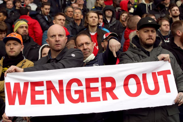 Fans hold up a Wenger Out banner in the stands