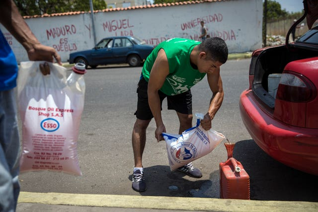 Jesus Gonzales fills a container with bagged gasoline he bought at extra cost at a fuel station