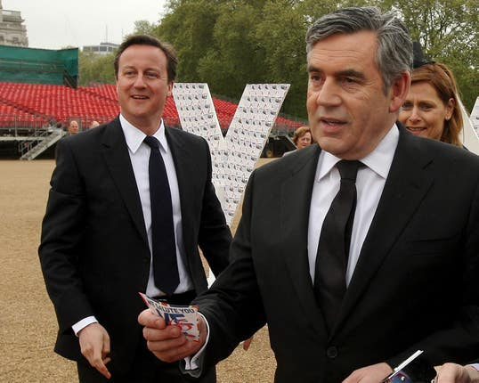 Prime Minister Gordon Brown prepares to add a message of thanks to a tribute to British servicemen, watched by his wife Sarah and Conservative Party leader David Cameron, at a VE Day reception in 2009
