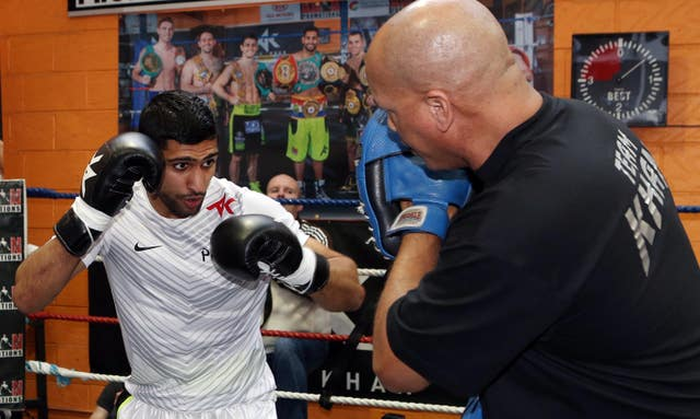 Khan's trainer Virgil Hunter (right) has urged him not to retire from boxing