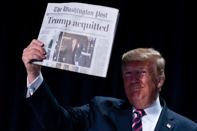 US President Donald Trump holds up a newspaper with a headline that reads 'Trump acquitted'