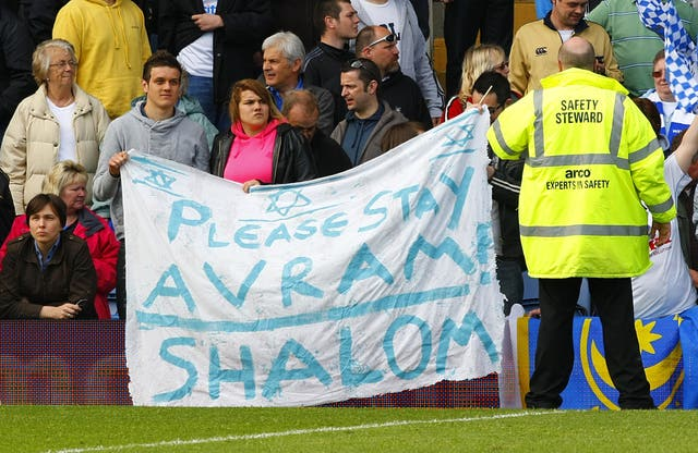Portsmouth fans hold up a sign which asks manager Avram Grant to stay at the club