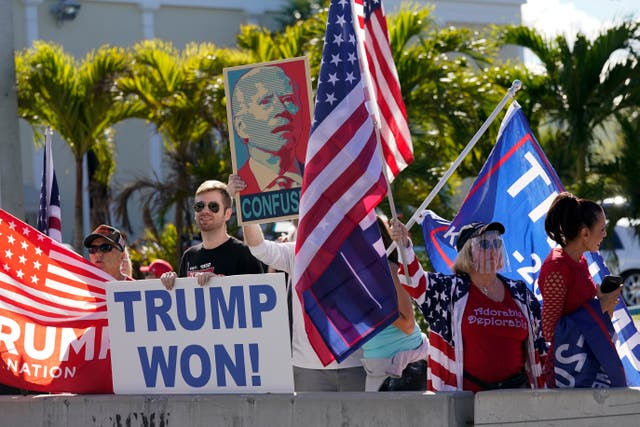 Supporters of Donald Trump wait for the motorcade on the road to Mar-a-Lago