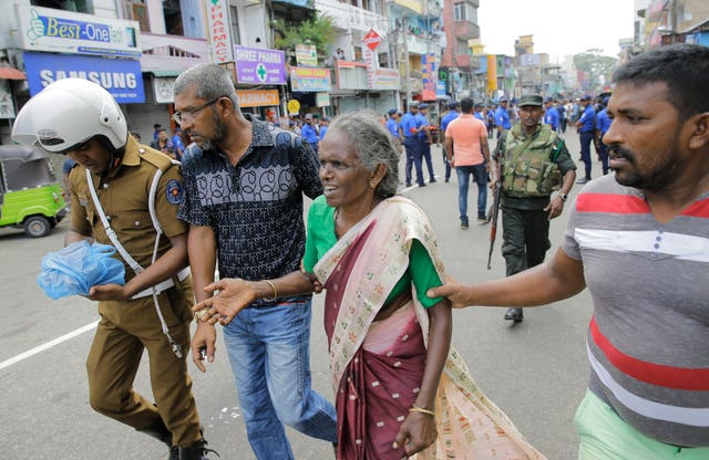 An elderly woman is helped near St Anthony's Shrine in Colombo