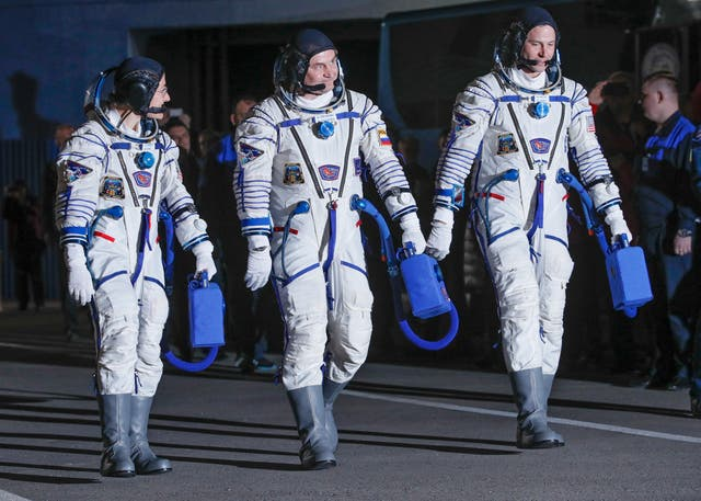 US astronauts Christina Koch, left, Nick Hague, right, and Russian cosmonaut Alexey Ovchinin