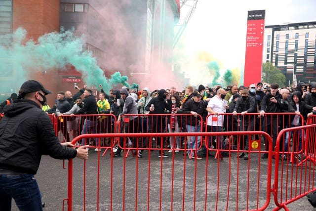 Fans move barriers outside Old Trafford as they let off flares