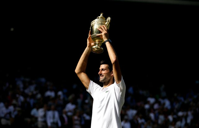 Novak Djokovic holds the Wimbledon trophy aloft for the fourth time