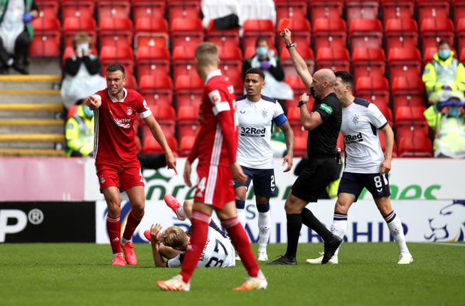 Aberdeen's Andrew Considine (left) is shown a red card