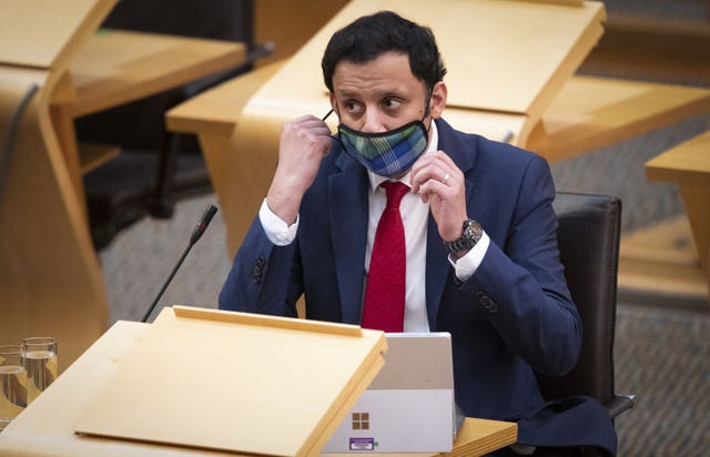 Anas Sarwar removing his mask in Holyrood