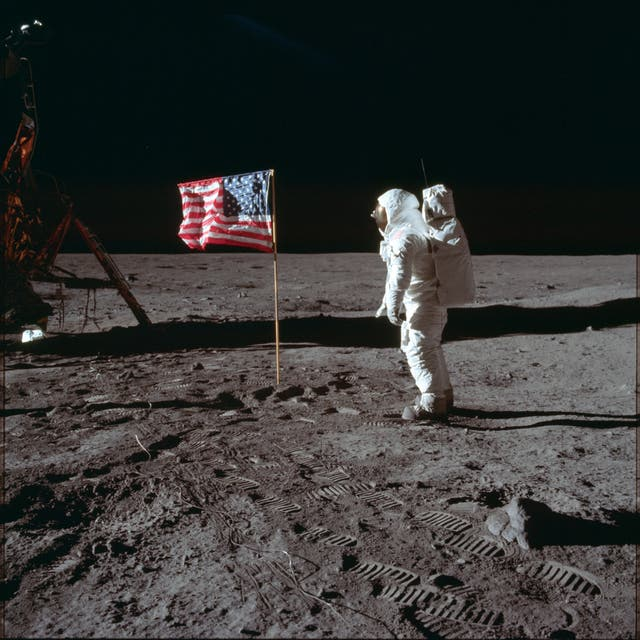 Astronaut Buzz Aldrin Jr poses for a photograph beside the US flag on the moon