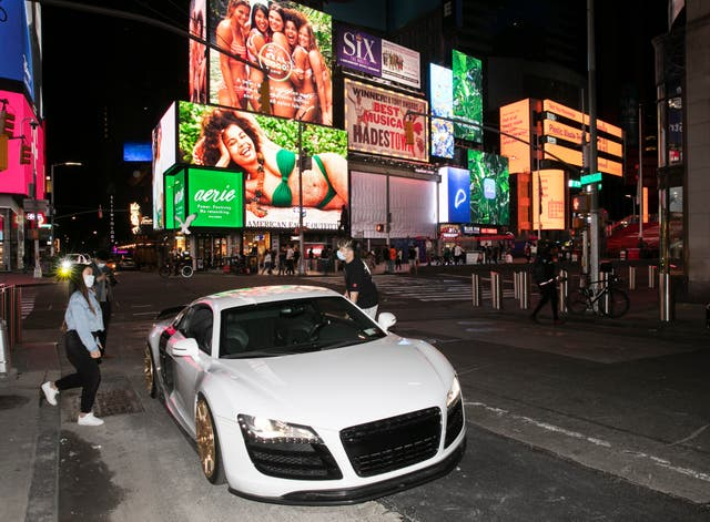 Claudia Luong and Danny Lin hop into his 2008 Audi R8 for a spin around New York's Times Square during the coronavirus pandemic