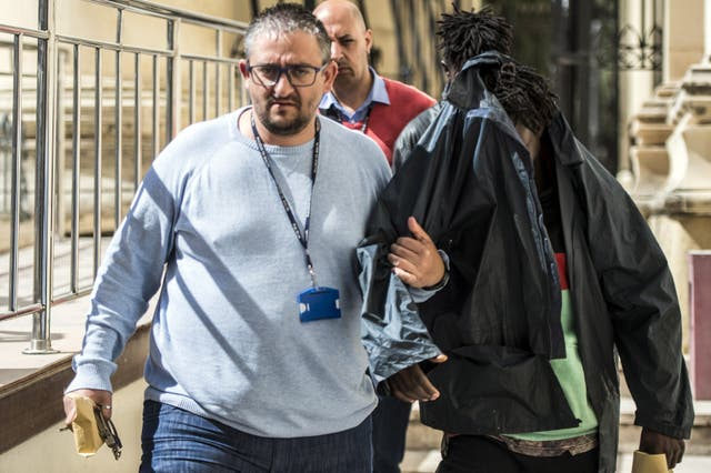 One of the three migrants accused of hijacking a vessel is escorted out of a couthouse in Valletta