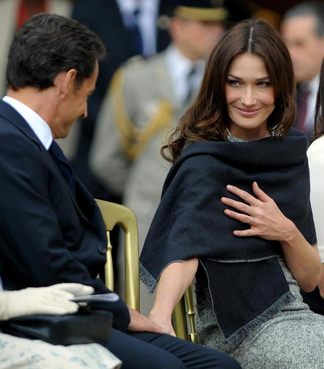 Carla Bruni-Sarkozy (right), looks to her husband President Nicolas Sarkozy, during a parade at The Royal Hospital Chelsea in London