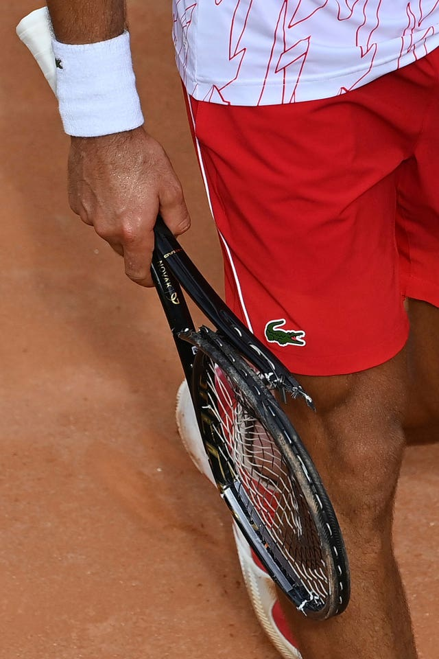Novak Djokovic carries his broken racket
