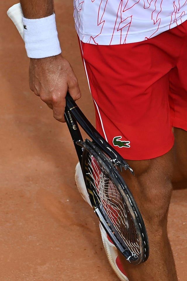 Novak Djokovic carries his broken racket