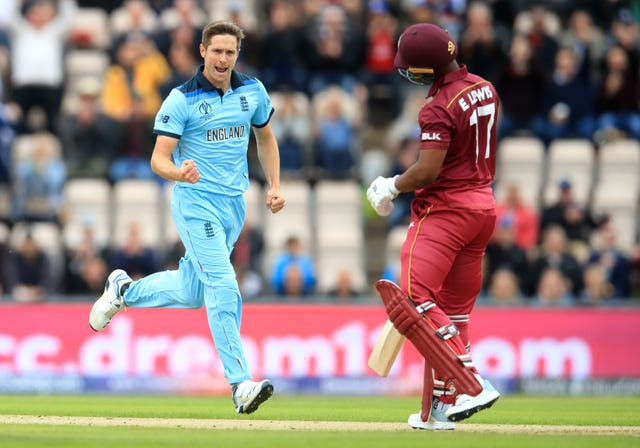 Chris Woakes celebrates taking England's first wicket of the day.
