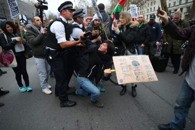 A person is held by police officers during a protest by Stop the War Coalition in Whitehall (Yui Mok/PA)